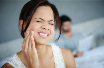 Woman Touching Jaw In Pain.